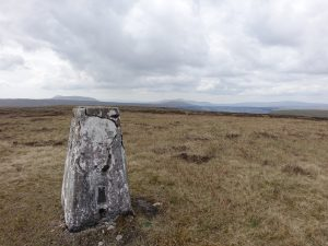 Trig on Yockenthwaite Moor with distant Pen-y-ghent and Ingleborough