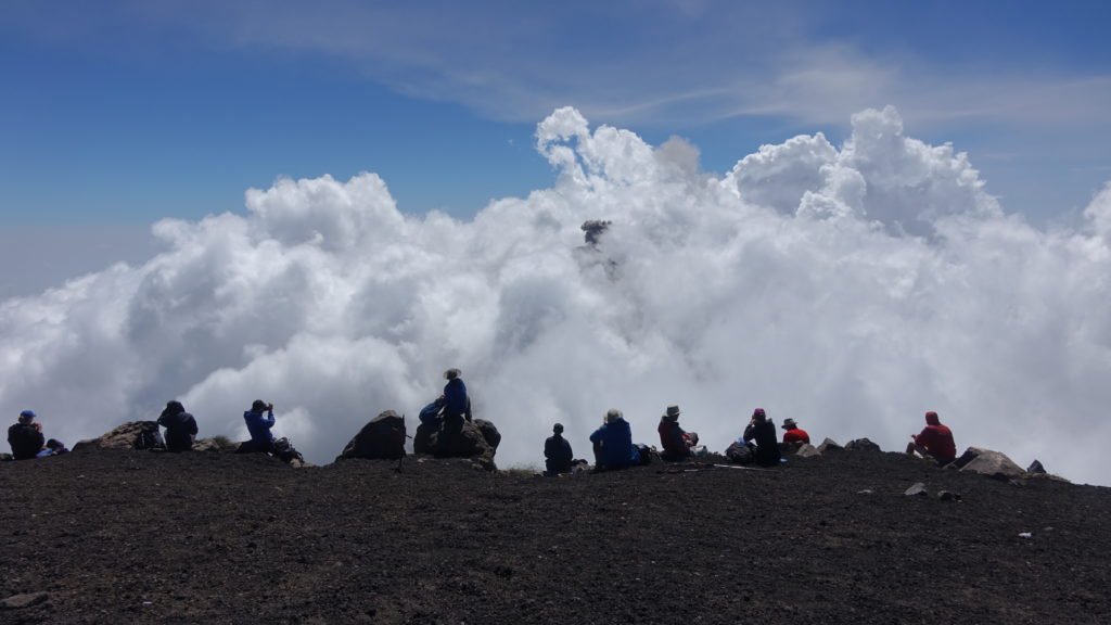 Group lunch as a puff of ash from Fuego rises above the cloud
