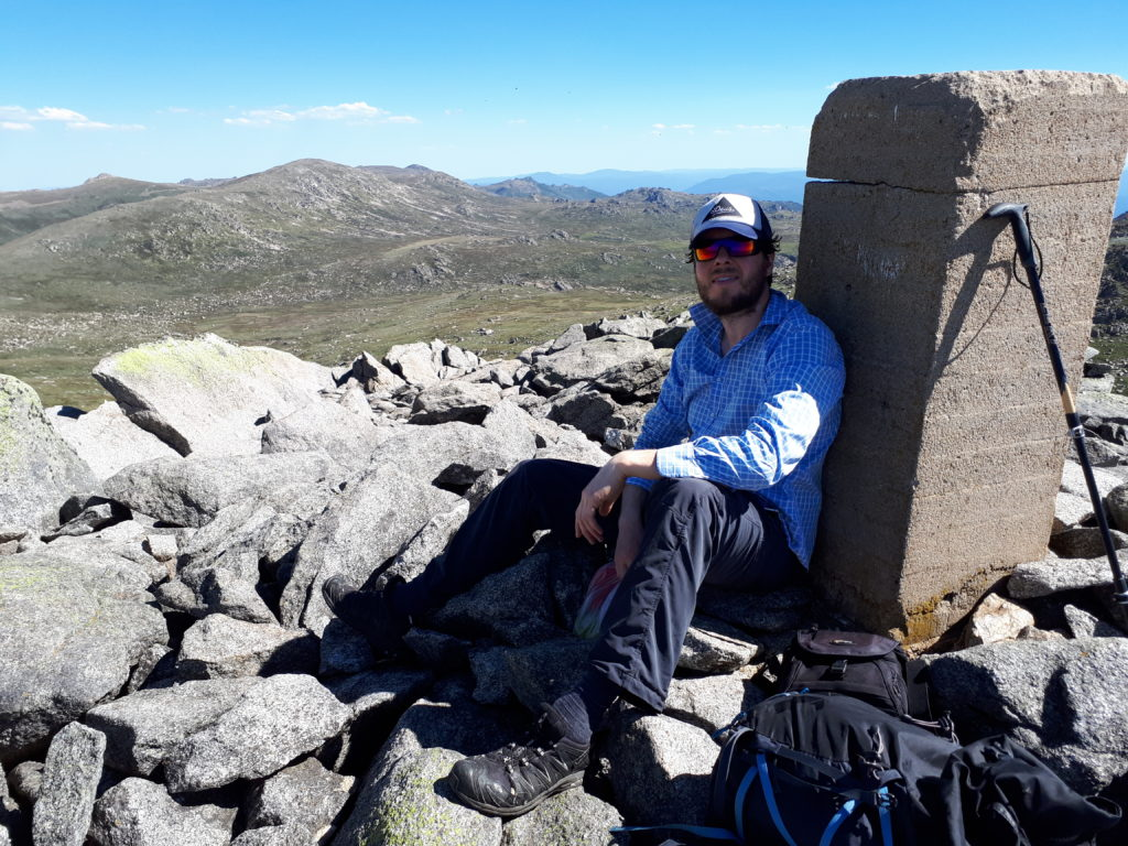 Mount Townsend summit with Mount Kosciuszko behind him