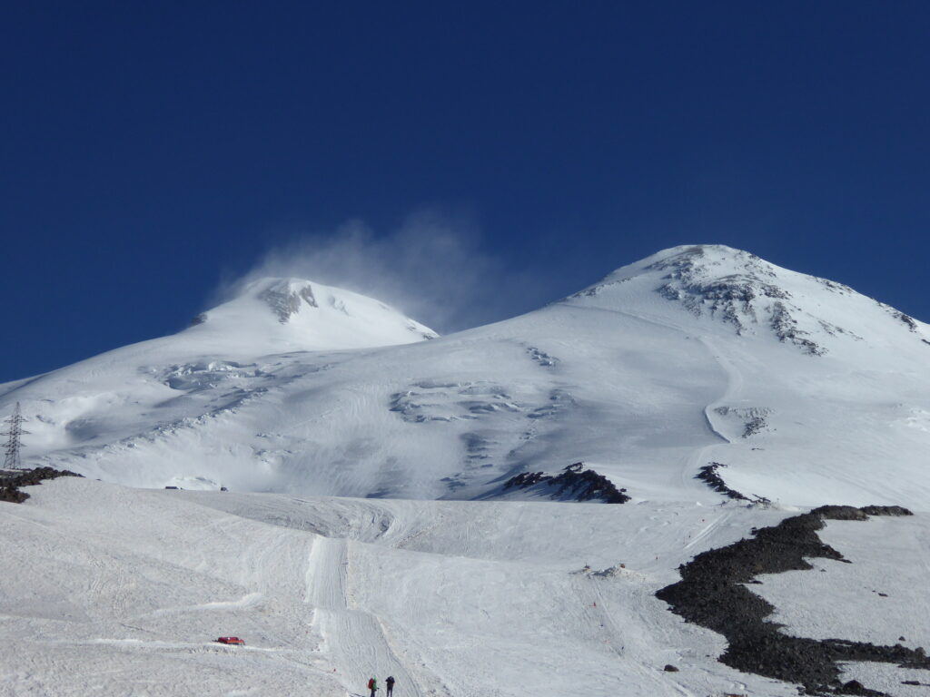 Storm winds blow snow off the west summit of Mount Elbrus